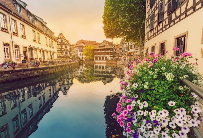 Travel landscape with half-timbered houses on the banks of the river ill and decorated flowers in Strasbourg. France and. Beautiful travel landscape with half stock images