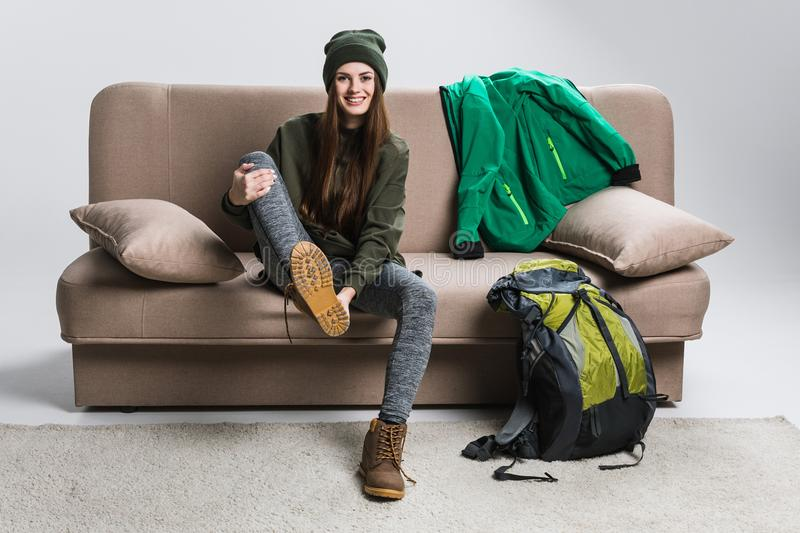 Beautiful traveler wearing hiking boots and warm clothing. On sofa royalty free stock photography