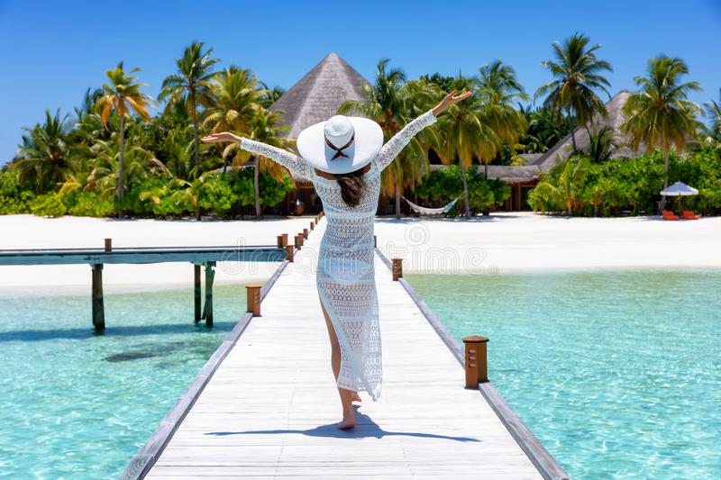 Woman walks over a wooden pier in the Maldives stock photos