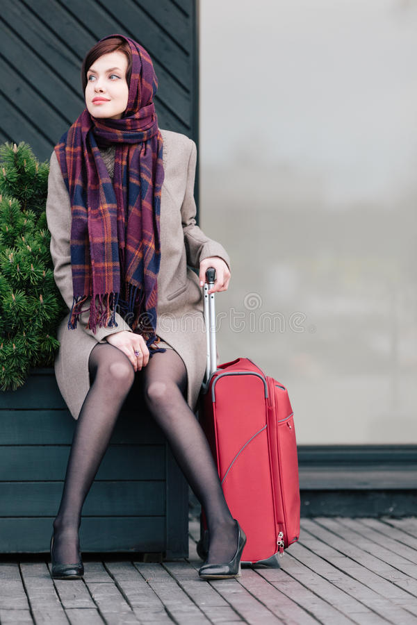 Beautiful traveller. Classy woman with suitcase is waiting for someone royalty free stock image