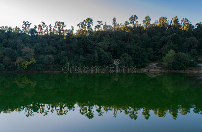 Beautiful tree line and its reflection in Deoria Tal during sunrise. royalty free stock image