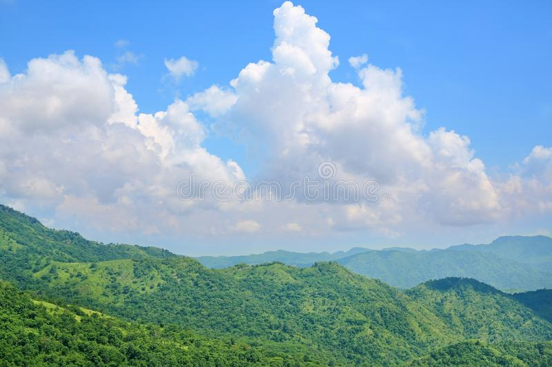 Beautiful trees and mountains on blue sky with white puffy cloud. Landscape view of nature.  stock image