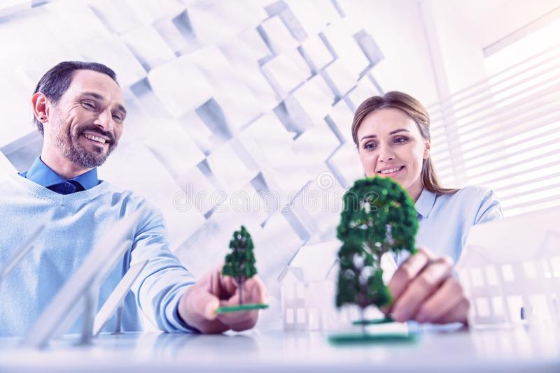 Happy architects smiling while placing beautiful miniature trees on the table royalty free stock photo