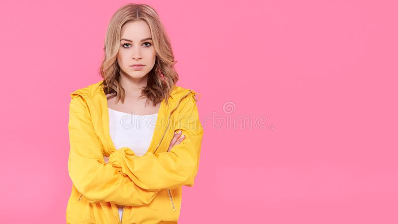 Beautiful trendy girl in bright yellow jacket and crossed arms. Attractive young woman portrait over pastel pink background. royalty free stock photo