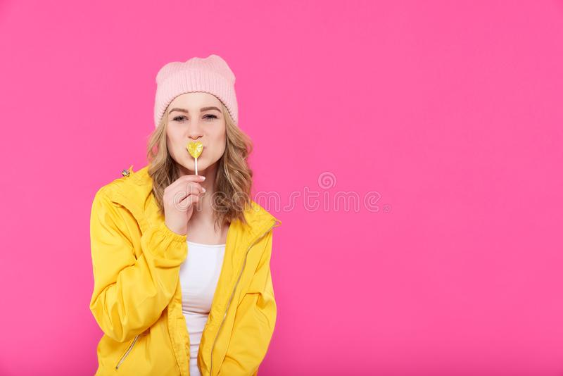 Beautiful trendy girl in colorful clothes and pink beanie kissing [he]art shaped popsicle. Co]ol y]oung woman fashion portrait. royalty free stock photos