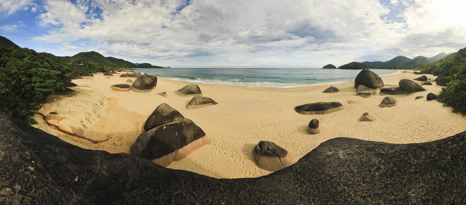 Beautiful tropical beach with big stones on shore and mountains. Panorama of beautiful tropical beach praia de fora with pure water, white sand, big stones and stock photography