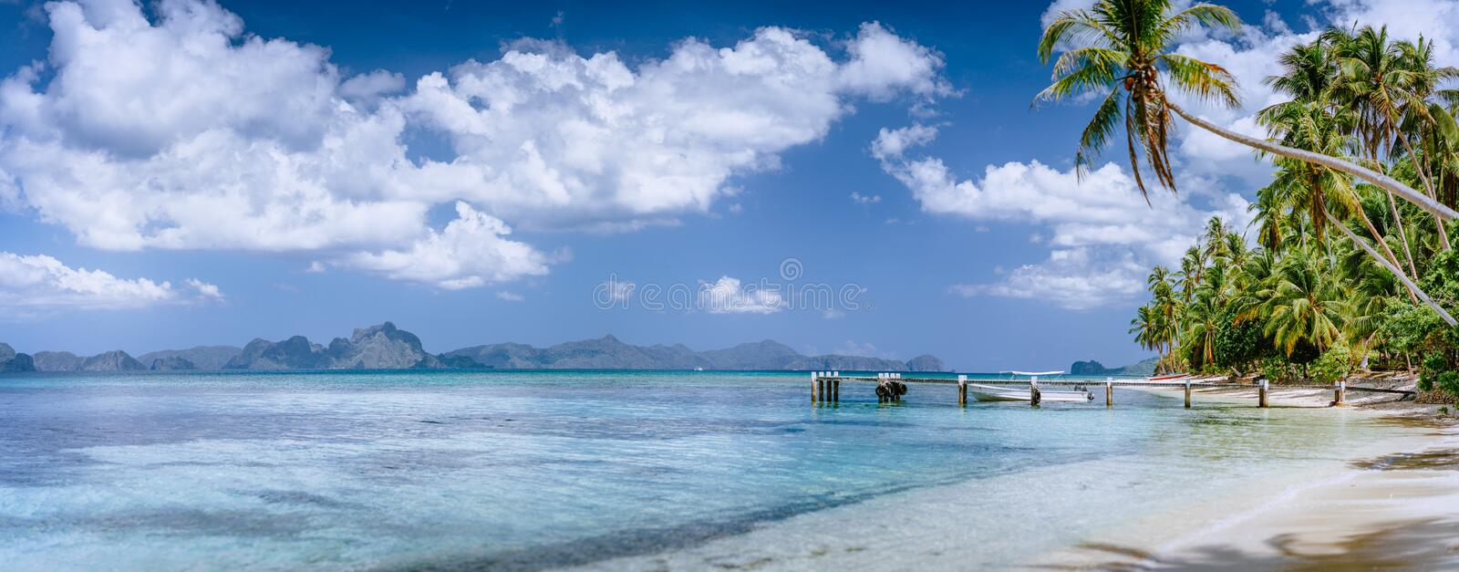 Beautiful tropical beach. Crystal clear lagoon with palms around and impressive white clouds. Holiday and paradise royalty free stock photos
