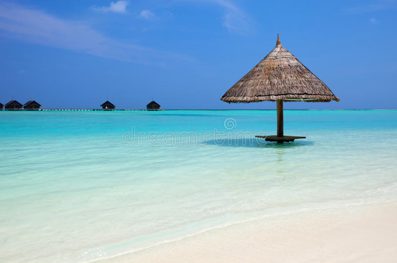 Beautiful tropical beach at Maldives. Tropical thatch umbrella on a beautiful beach at Maldives stock photos