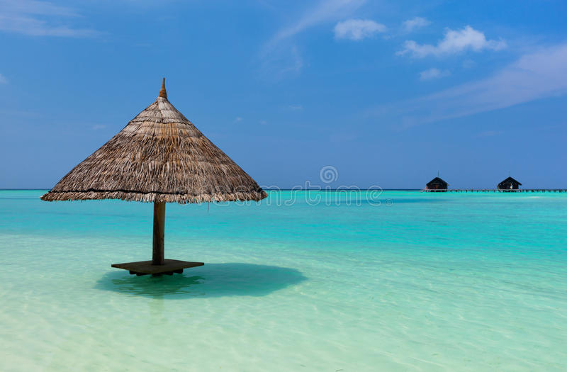 Beautiful tropical beach at Maldives. Tropical thatch umbrella in a water on a beautiful beach at Maldives royalty free stock images