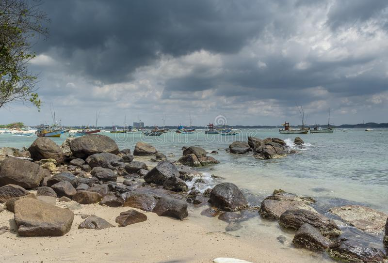 Beautiful tropical beach with rocks during cloudy day royalty free stock photos