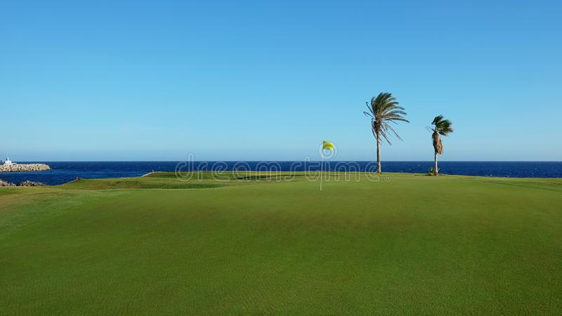 Beautiful tropical golf course fairway with a yellow flagstick, at the edge of the Atlantic Ocean royalty free stock photo