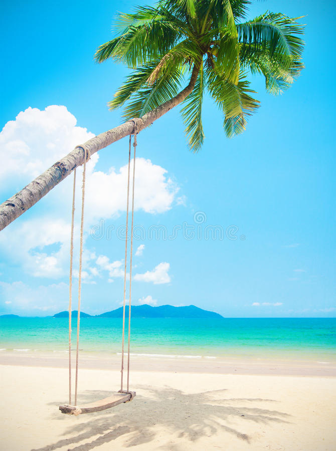 Beautiful tropical island beach with coconut palm trees and swing royalty free stock photo