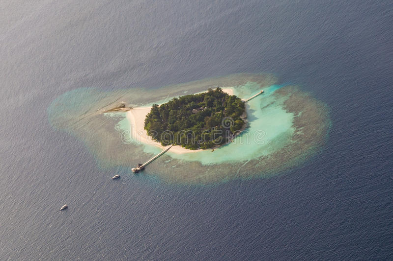 Beautiful tropical island at ocean arial view from seaplane at Maldives royalty free stock images