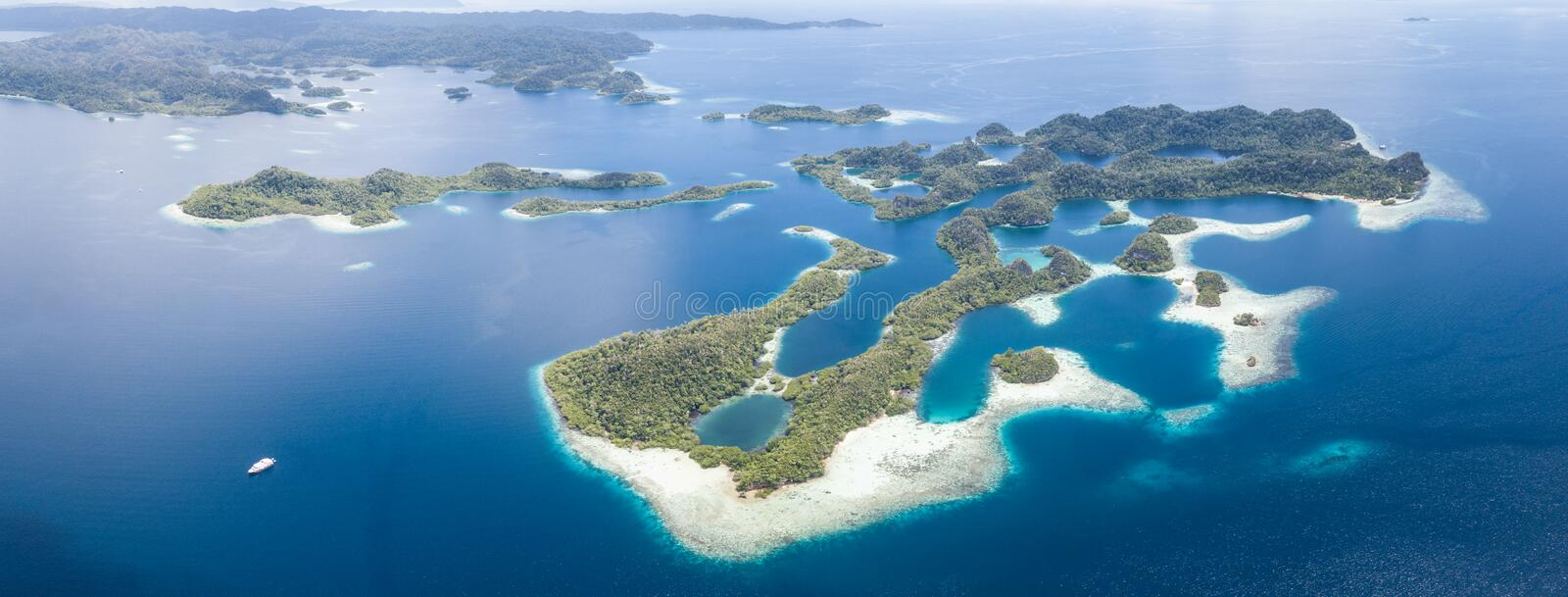Aerial View of Idyllic Tropical Islands in Raja Ampat. The beautiful tropical islands of Pef are surrounded by calm seas in the equatorial seascape of Raja Ampat royalty free stock photo