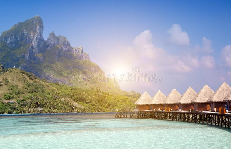 Beautiful tropical Maldives island, water villas, bungalow on sea and the mountain on a background stock image