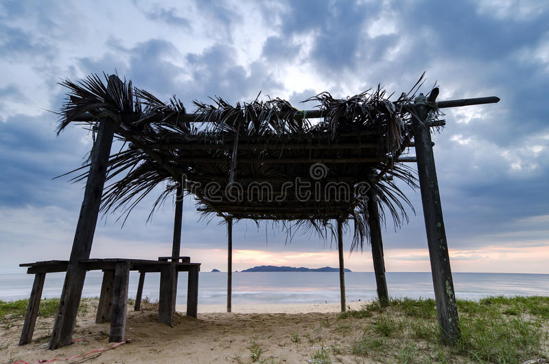 Beautiful tropical sea view scenery through wooden cottage. fronds roof, sandy beach and cloudy sky stock photos