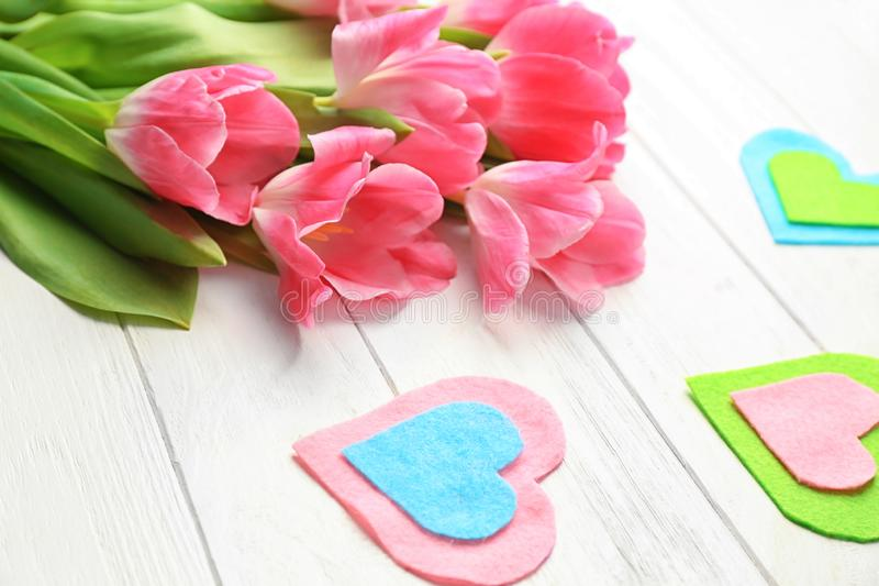 Beautiful tulips and decorative felt hearts on white wooden background stock photos
