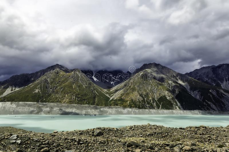 Beautiful turqouise Tasman Glacier Lake and Rocky Mountains in the clouds, Mount Cook National Park, New Zealand royalty free stock photos