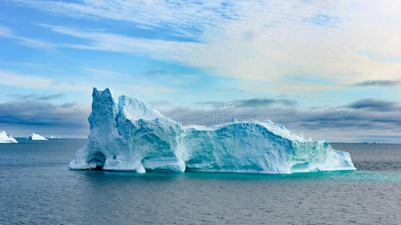 Icebergs in Greenland. Colorful huge Iceberg building with tower and gate. Beautiful turquoise and blue iceberg with shiny water refections near Ilulissat stock photography