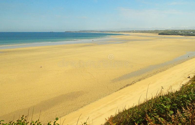 Porthkidney Sands Hayle Estuary, Hayle Cornwall England. Beautiful turquoise and blue sea and golden sand, grassy sea dunes and sunny summers day at Hayle royalty free stock photo