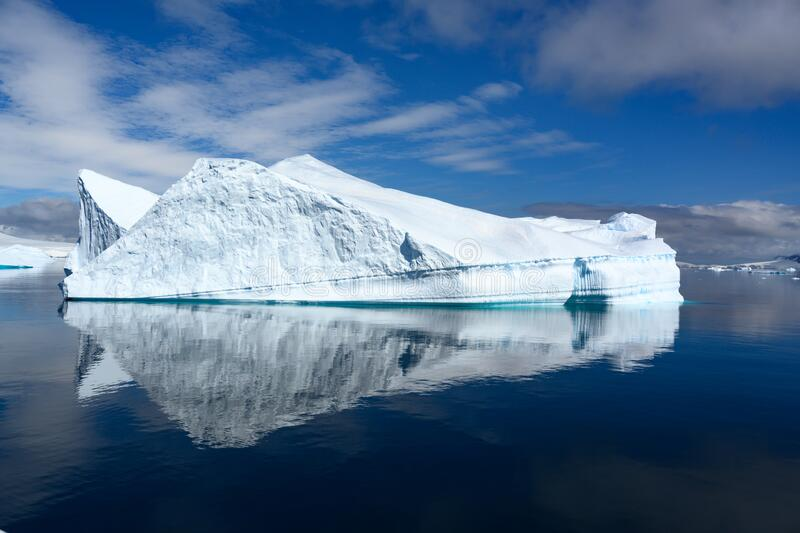 Beautiful turquoise iceberg with texture and cave on beautiful day in Antarctica reflecting in calm water royalty free stock photography