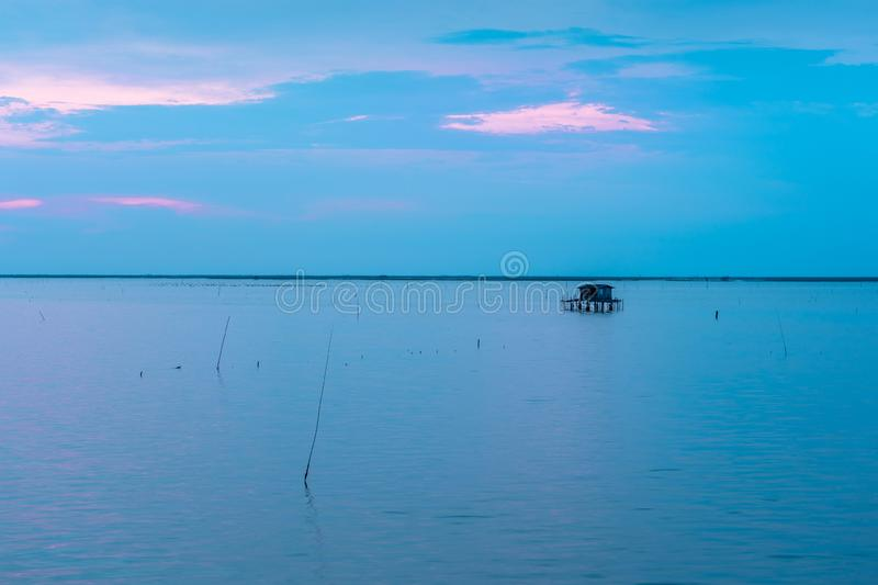 Beautiful twilight with silhouette of fisherman house on ocean royalty free stock image