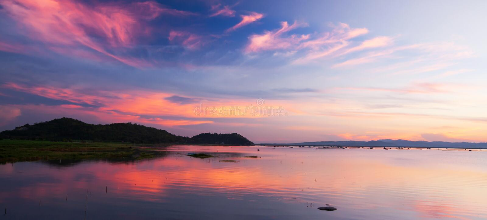 Beautiful twilight sky above a tropical lake, gently light pink clouds against the blue sky at dusk. Soft reflection of clouds and mountains on surface of stock image