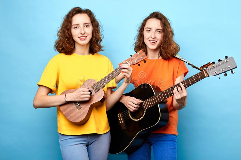 Beautiful twins female musicians playing the guitar. Isolated blue background. hobby, interest, lifestyle stock photo