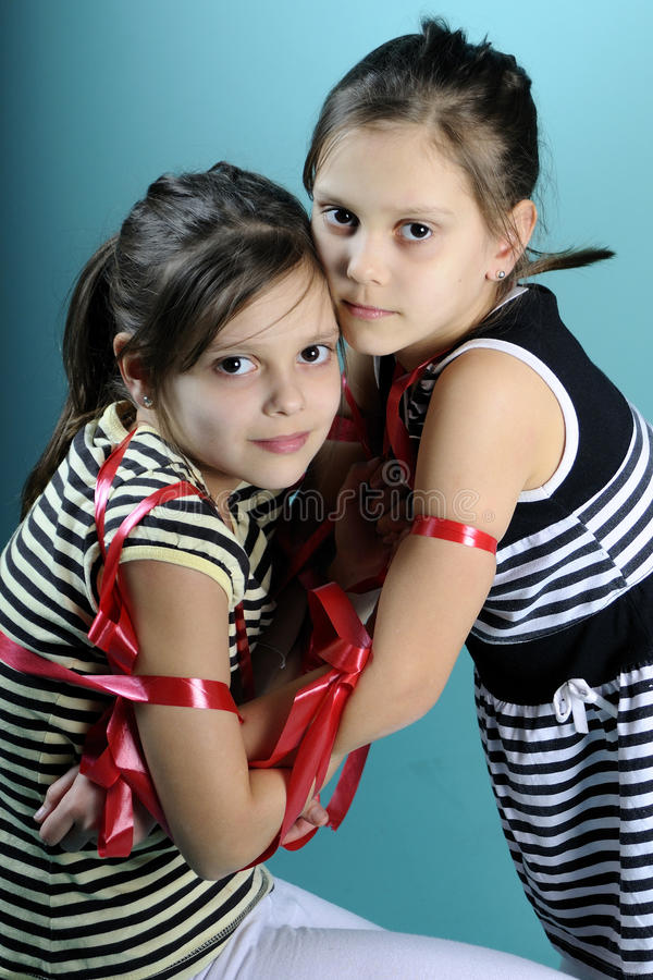 Beautiful twins portraits. Twin white sisters exercising with red accessory, turquoise background stock photo