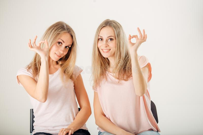 Beautiful twins women with natural make-up and long hair showing gesture ok. stock images
