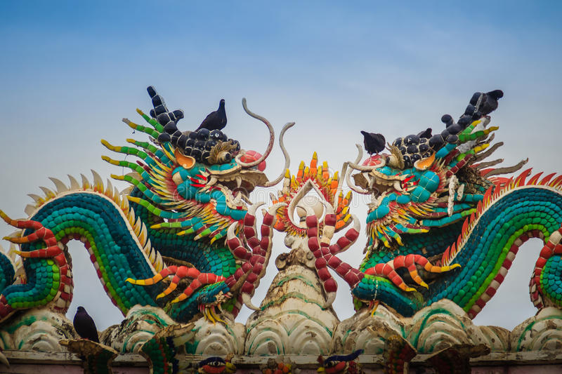 Beautiful two large grimace dragons crawling on decorative tiles. Roof in Chinese temple. Colorful roof detail of traditional Chinese temple with two dragon on royalty free stock photo
