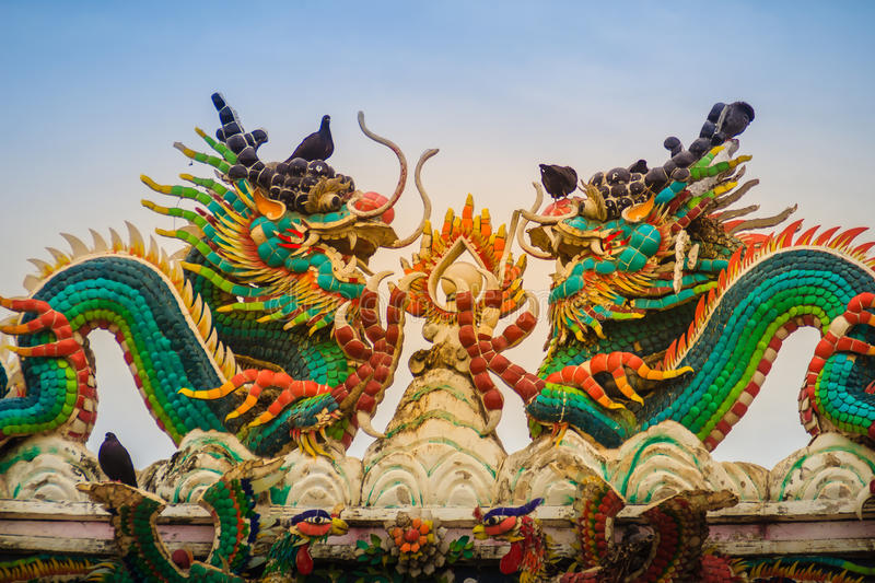 Beautiful two large grimace dragons crawling on decorative tiles. Roof in Chinese temple. Colorful roof detail of traditional Chinese temple with two dragon on stock image