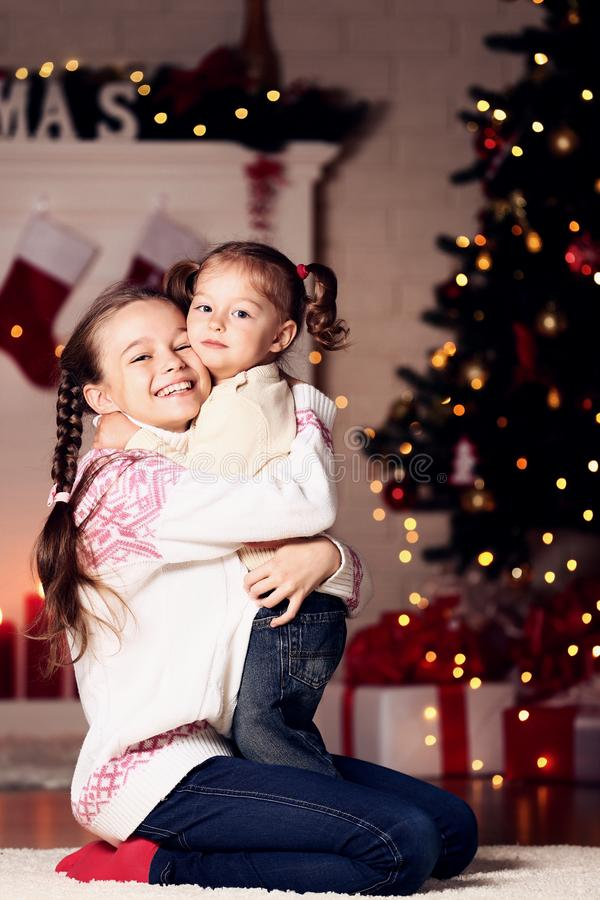 Two sisters near christmas tree royalty free stock photos