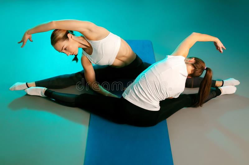 Beautiful two young slim gymnast women in sports clothing stretching on the floor on fitness mat in neon lights stock photo