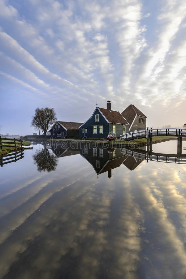 Dutch house mirrored on the calm canal. Beautiful and typical Dutch wooden houses architecture mirrored on the calm canal of Zaanse Schans located at the North royalty free stock photography