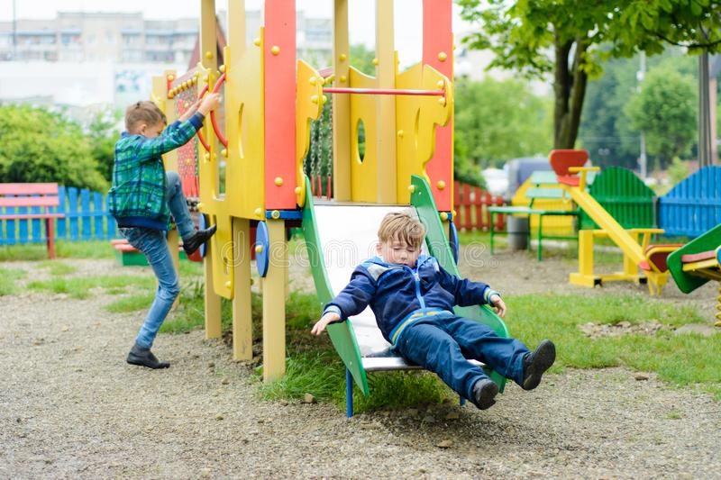 Funny children play on a children`s playground stock photo