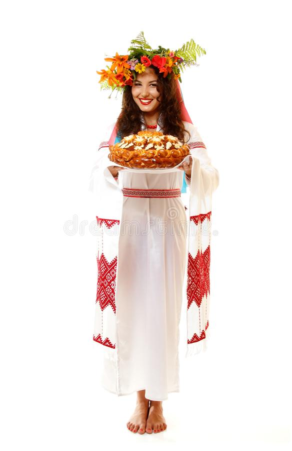 Beautiful ukrainian young hospitable woman in native costume by. Tradition holding embroidered towel and round loaf, on white background stock photos