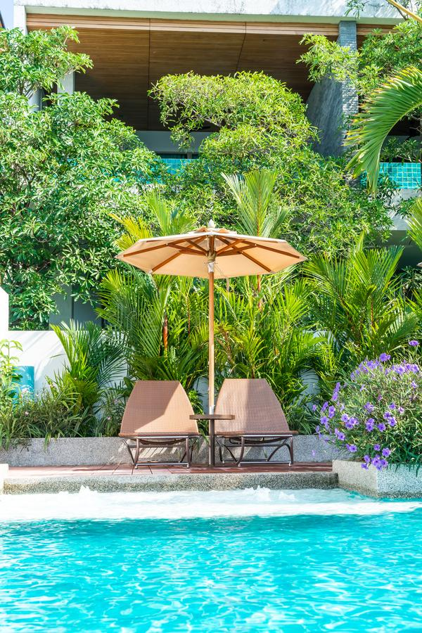 Beautiful umbrella and chair around swimming pool in hotel and resort - vacation concept. Beautiful umbrella and chair around swimming pool in hotel and resort stock photography