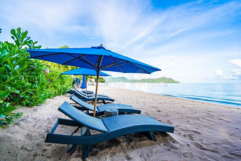 Beautiful umbrella and empty bed chair on the tropical beach and sea with white cloud blue sky background royalty free stock photos