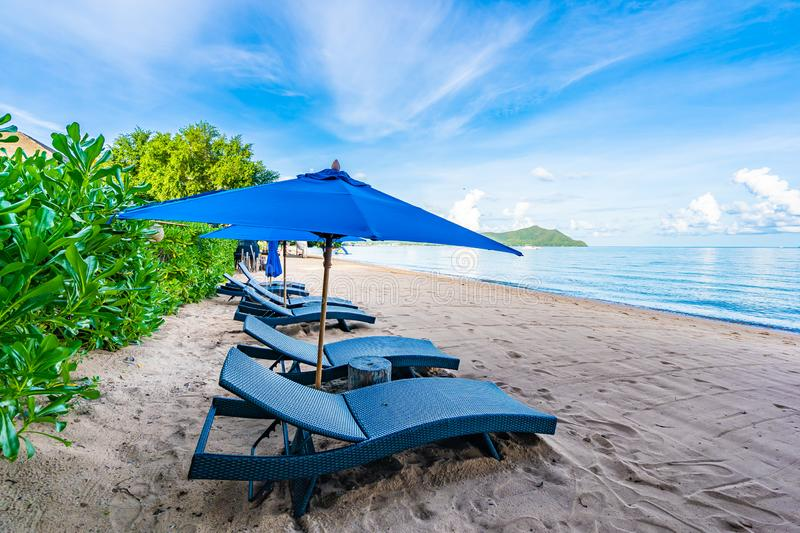 Beautiful umbrella and empty bed chair on the tropical beach and sea with white cloud blue sky background stock photos