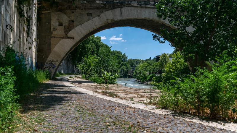 Beautiful under the bridge landscape in Rome. River, water, green, bushes, trees, wall, path, blue, sky, sunny stock photography