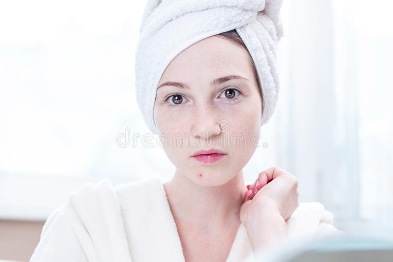 Beautiful unhappy young woman detects acne on her face. Concept of hygiene and care for the skin. Beautiful unhappy young woman with a towel on her head detects stock photography
