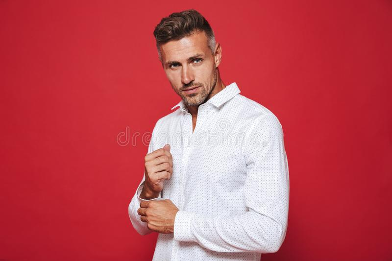 Beautiful unshaved man 30s in white shirt looking on camera, iso. Beautiful unshaved man 30s in white shirt looking on camera isolated over red background stock images