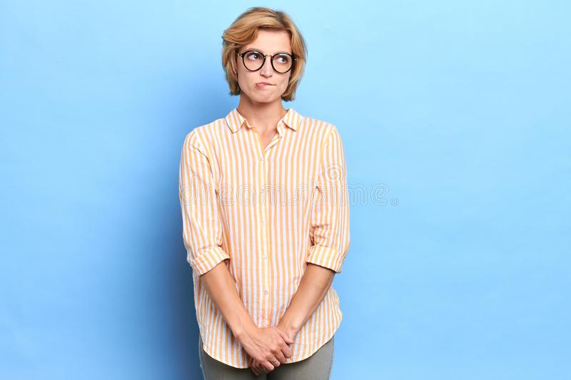 Beautiful unsure shy timmid young blond student in glasses biting her lips royalty free stock image