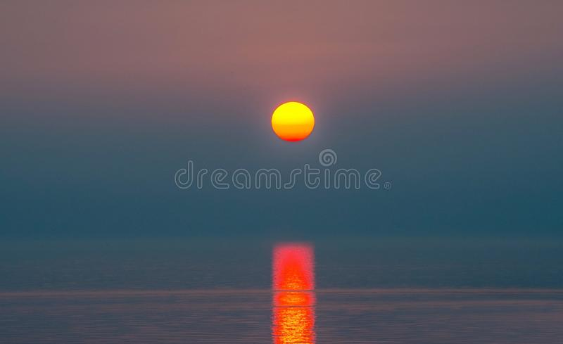 Beautiful unusual sunset over Lake Michigan. A Beautiful unusual sunset over Lake Michigan creates a single ray of light on a totally calm lake royalty free stock photos