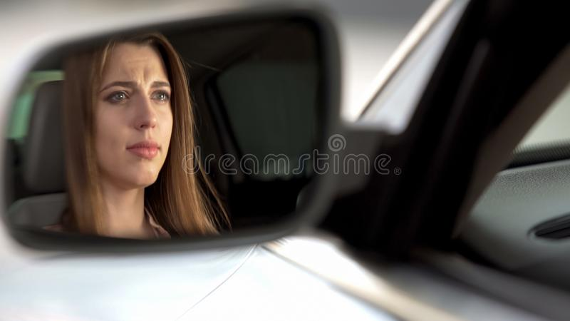 Beautiful upset woman sitting in automobile and crying, break-up and sadness royalty free stock photo