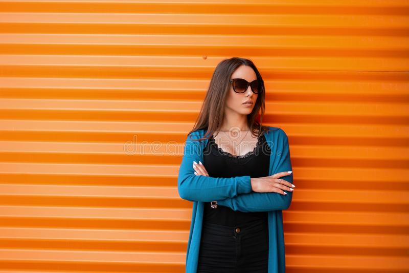 Beautiful urban hipster woman in blue knitted cape in a stylish black top in jeans in trendy dark sunglasses is posing. Near a metallic orange building on the royalty free stock photography