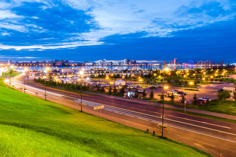 Beautiful urban landscape with a road, a Park and a lake at sunset royalty free stock images
