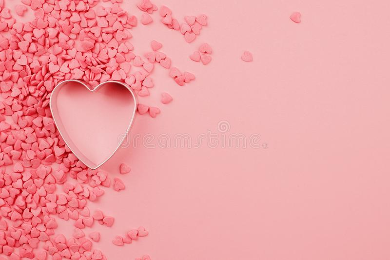 Beautiful valentines day background with baked mold heart-shaped and coral pink confectionery hearts on pink monochrome paper,. Trendy color 2019, abstract royalty free stock images