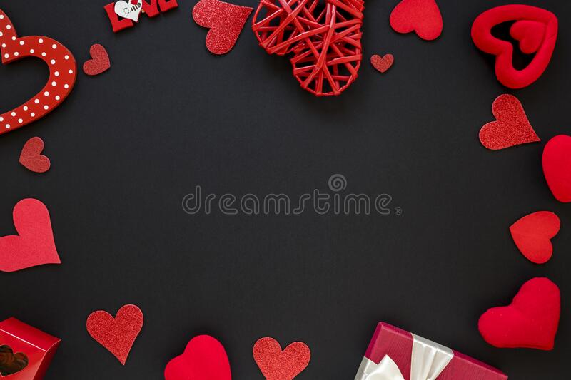 Heart shape made from ribbon on red stock image